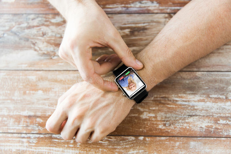 Close up of hands with incoming call on smartwatch. Business, modern technology, communication and people concept - close up of male hands setting smart watch stock images