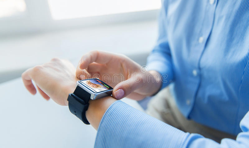 Close up of hands with incoming call on smartwatch. Business, technology, communication and people concept - close up of woman hands with incoming call on smart royalty free stock photo
