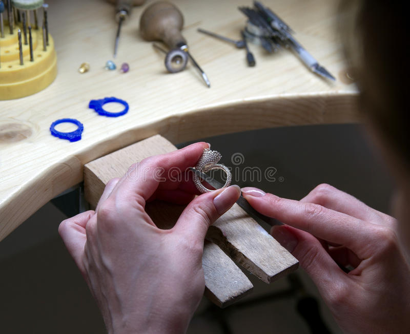 Close-up of the hands of a jewelle. Hands working jeweler at jeweller's workshop , handwork royalty free stock photo