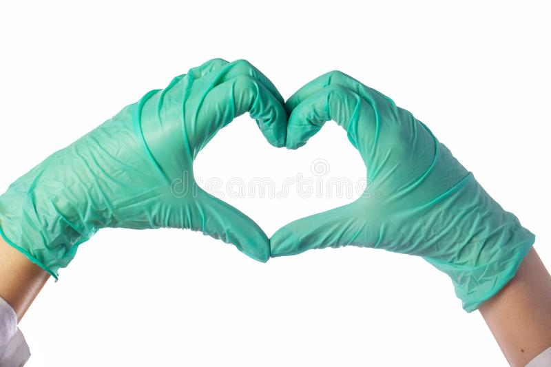 Close-up of hands in latex gloves. The heart is folded from the hands. Valentine card. Close-up of hands in green latex gloves. The heart is folded from the stock photo