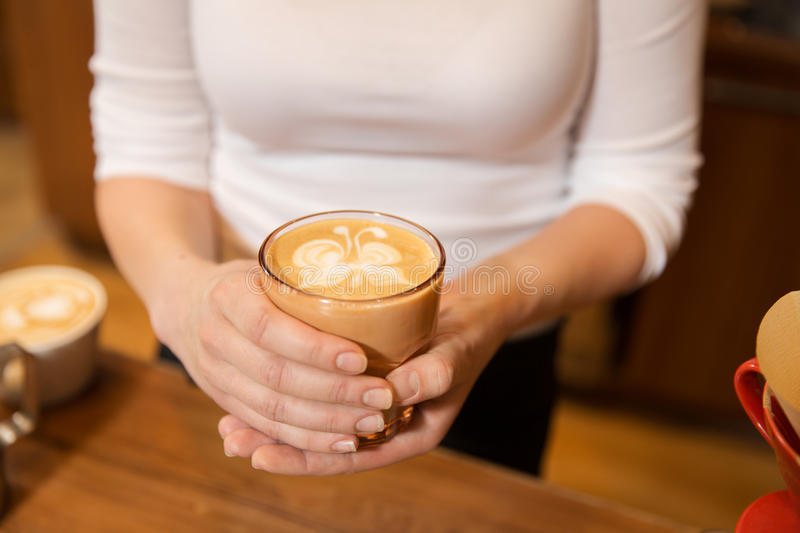 Close up of hands with latte art in coffee cup stock photo
