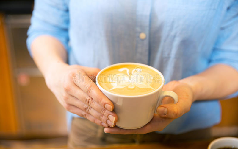 Close up of hands with latte art in coffee cup stock photos