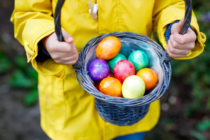 Close-up of hands of little child with colorful Easter eggs in basket royalty free stock photography