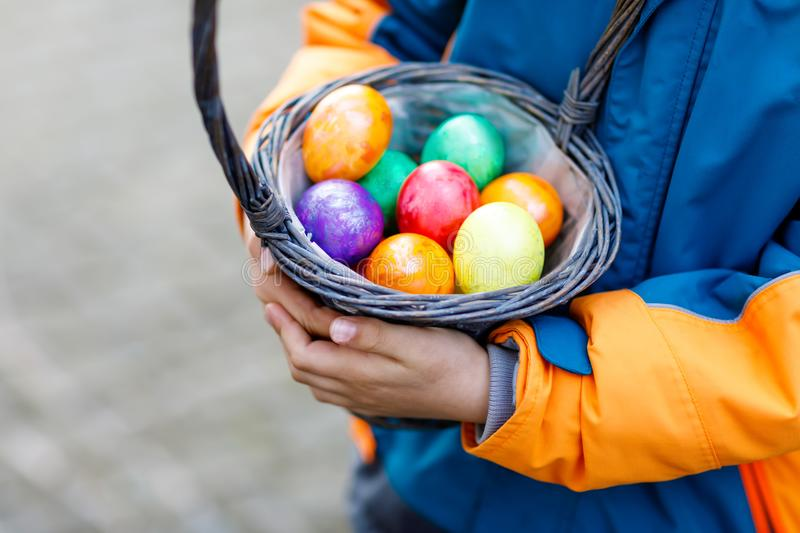 Close-up of hands of little child with colorful Easter eggs in basket royalty free stock image
