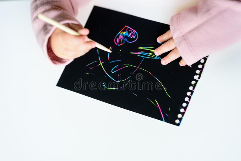 Close up of the hands of a little child drawing on magic scratch painting paper with drawing stick. royalty free stock photography
