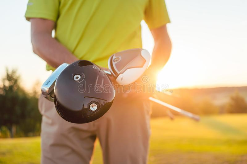 Close-up of the hands of a male professional player holding golf clubs stock image