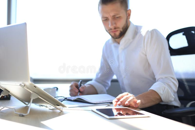 Close up hands of man touching tablet, multitasking on screen in an office royalty free stock photography