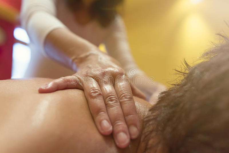 Close up of hands massaging female neck and shoulders. stock images