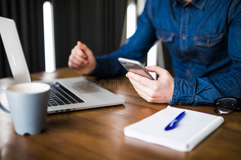 Close up hands multitasking man using laptop and cellphone connecting wifi, notebook and coffee cup. In office royalty free stock images