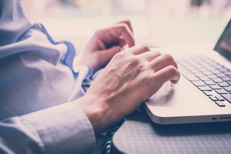 Close up hands multitasking man using laptop stock images