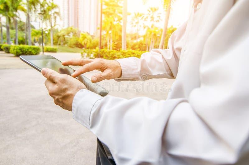 Close up hands multitasking man using tablet stock image