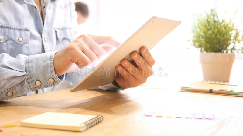 Close up hands multitasking man using tablet at work Desk. High quality stock photos