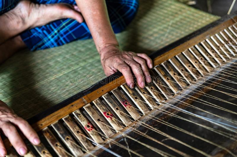 Close-up on the hands of an old woman weaving sedge mat in Ben Tre, Mekong delta region, Vietnam. Close-up on the hands of an old woman weaving sedge mat in the royalty free stock photo