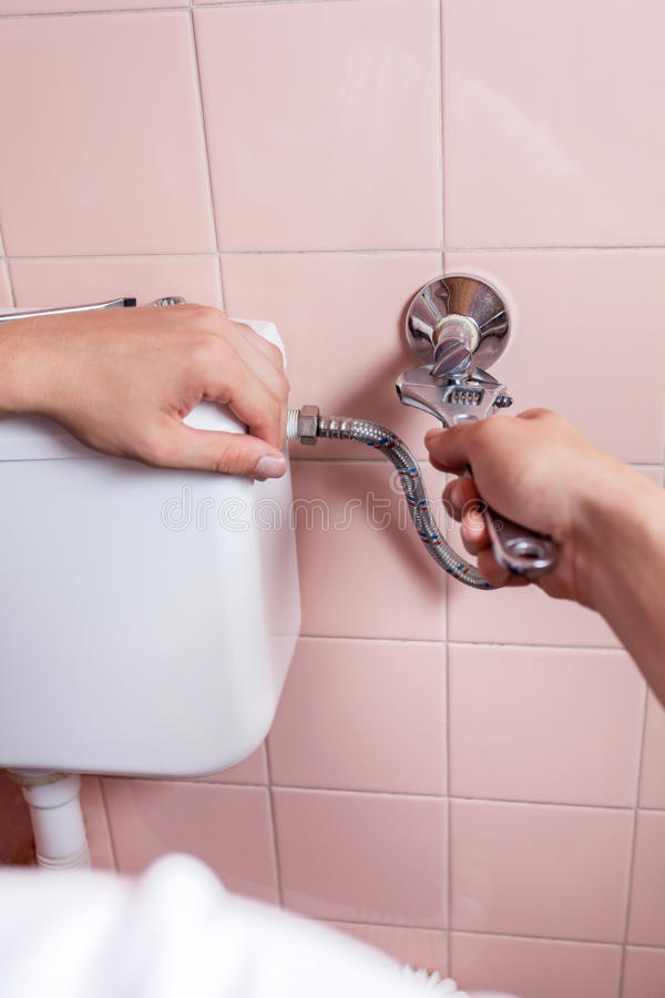 Close-up of a hands repairing toilet royalty free stock photography