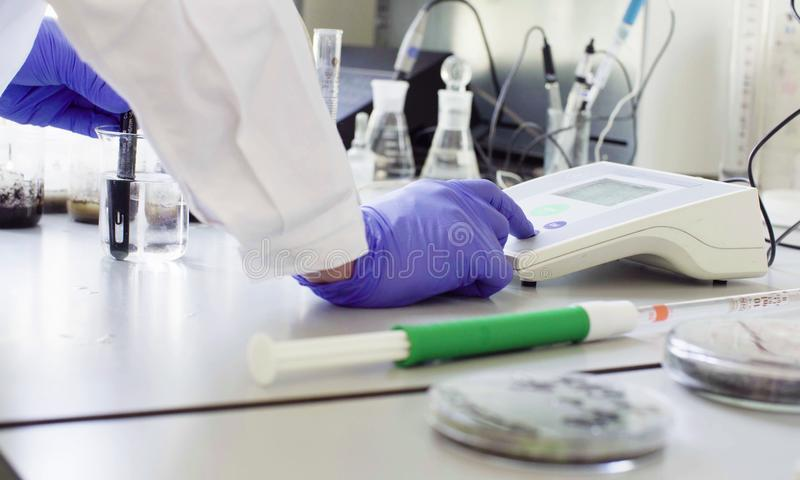 Hands of a scientist setting up an electronic pH meter royalty free stock photo