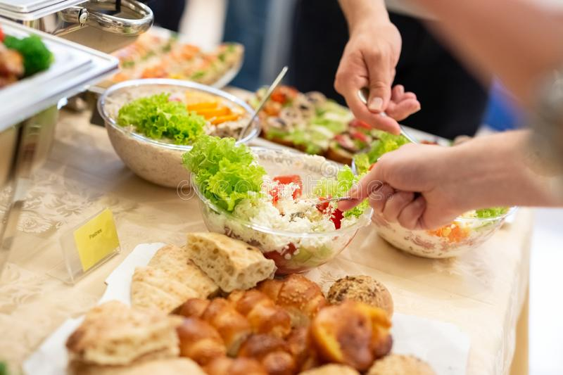 Close up of hands scooping food. Buffet catering meal concept restaurant or hotel concept royalty free stock photos