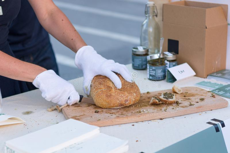 Close up of hands slicing bread for tasting at outdoor market place. royalty free stock photos