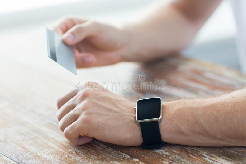 Close up of hands with smart watch and credit card. Business, technology, cash free and internet people concept - close up of male hands with smart watch and stock photo