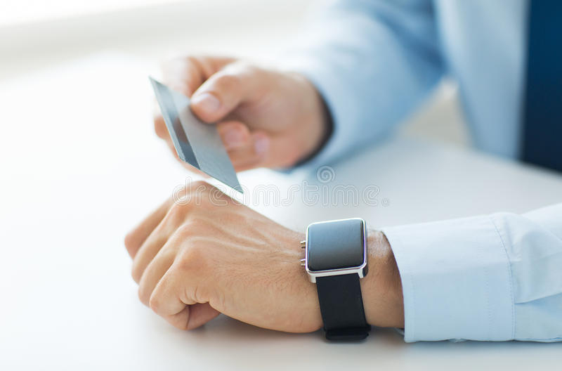 Close up of hands with smart watch and credit card. Business, technology, cash free and internet people concept - close up of male hands with smart watch and stock photography