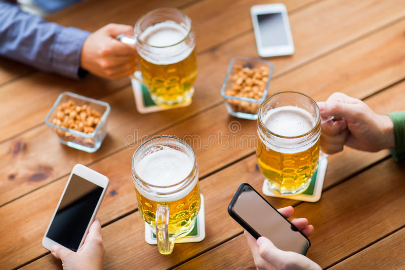 Close up of hands with smartphones and beer at bar. People, leisure, friendship and technology concept - close up of friends with smartphones and snacks drinking stock images