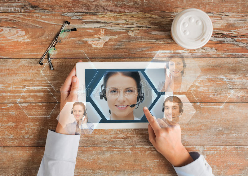 Close up of hands with tablet pc and helpline stock photos