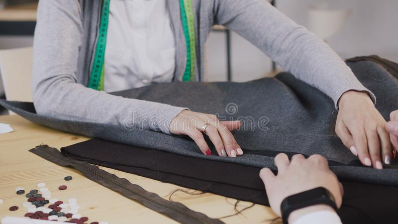 Close-up of a hands of tailored fashion designers working with materials, they sitting at the beautiful atelier with. Different tailoring tools and clothes. Two royalty free stock photo