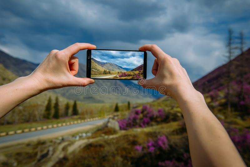 Close-up of hands taking photo or video on the smartphone. Unknown person shoots a stunning mountain landscape on a cloudy day. Focus on the gadget screen royalty free stock images
