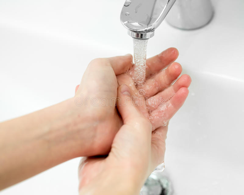 Close-up of hands under stream of water from faucet. Hands under stream of water from faucet stock photography