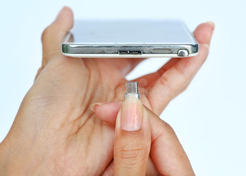Close-up hands of woman connects plug of charger mobile phone or smartphone charging on white background royalty free stock image