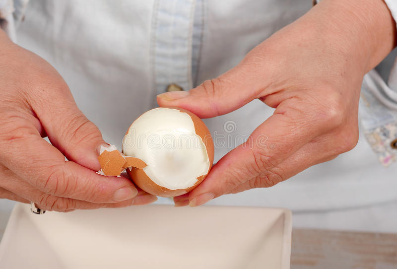 Close up of hands of woman shells hard-boiled egg. Close up of hands of woman shells a hard-boiled egg stock photo