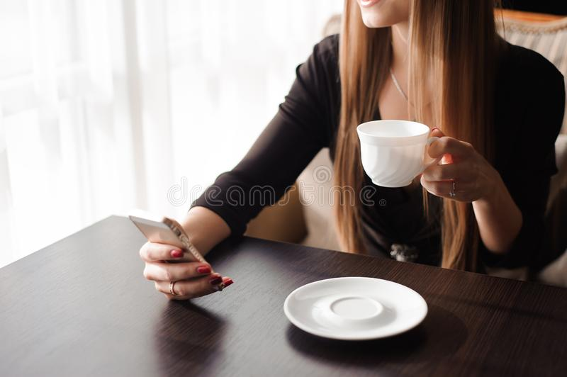 Close up of hands woman using her cell phone in restaurant, cafe. stock photography