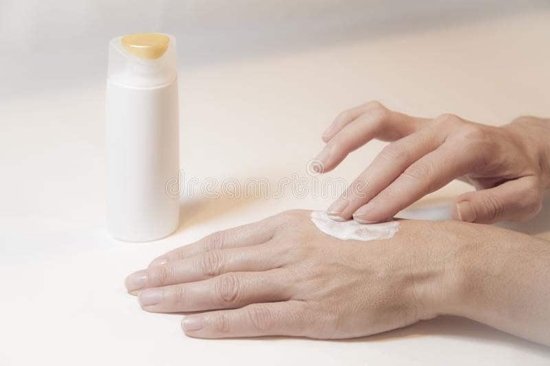 Close up of the hands of a woman who takes care of herself by rubbing cream with two fingers on the back of her left hand royalty free stock images