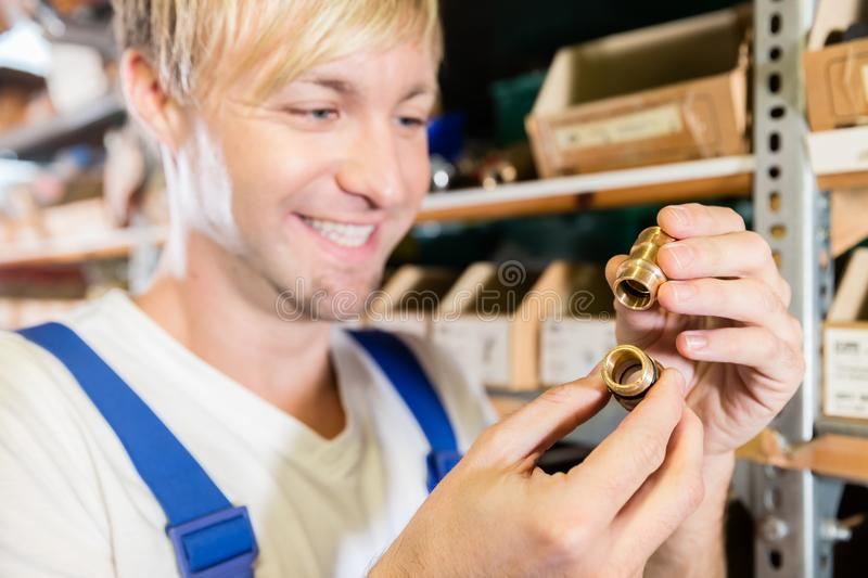 Close-up of the hands of a worker holding two pipe fitting accessories royalty free stock photos