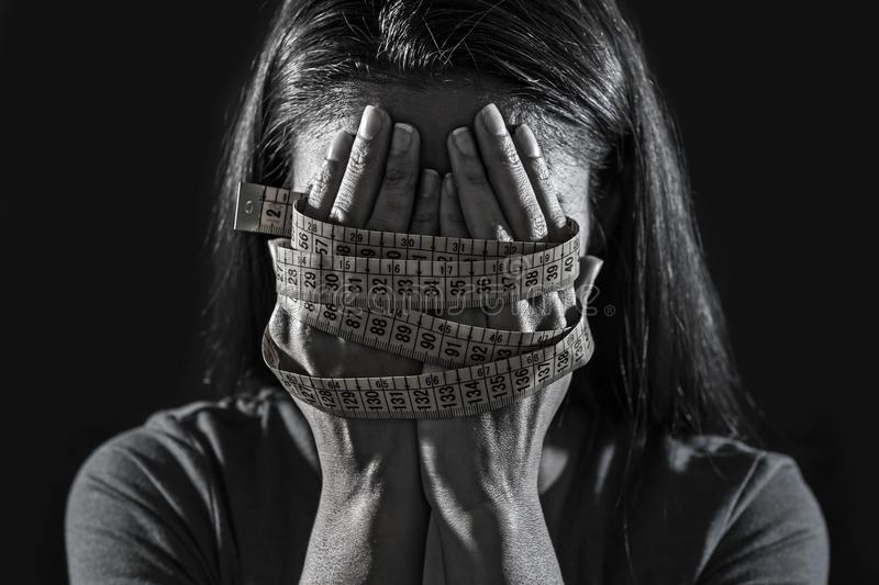 Hands wrapped in tailor measure tape covering face of young depressed and worried girl suffering anorexia or bulimia nutrition dis stock images