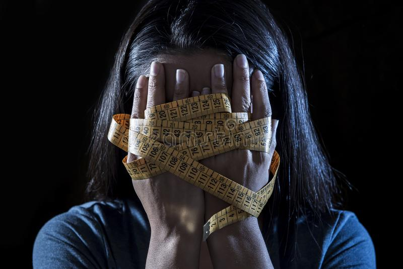 Hands wrapped in tailor measure tape covering face of young depressed and worried girl suffering anorexia or bulimia nutrition dis stock photos