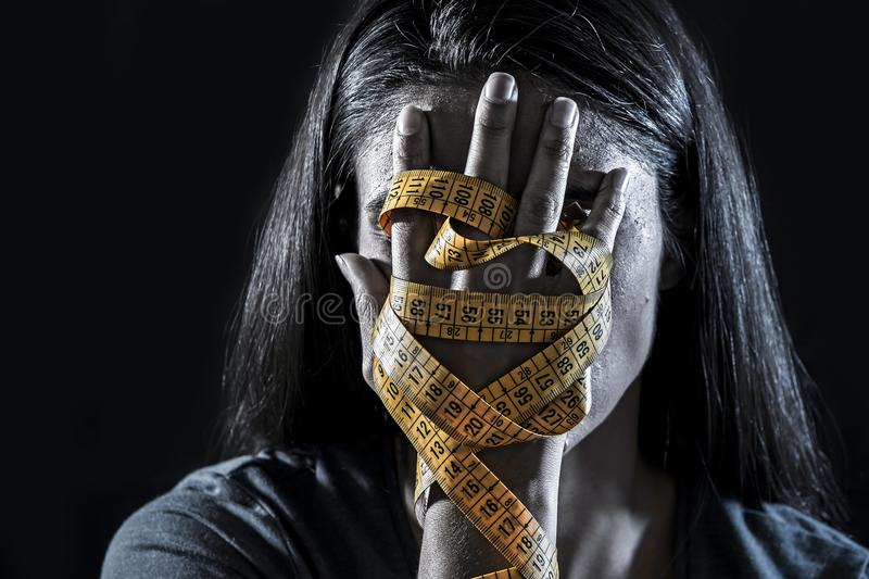 Hands wrapped in tailor measure tape covering face of young depressed and worried girl suffering anorexia or bulimia nutrition dis. Close up hands wrapped in royalty free stock image