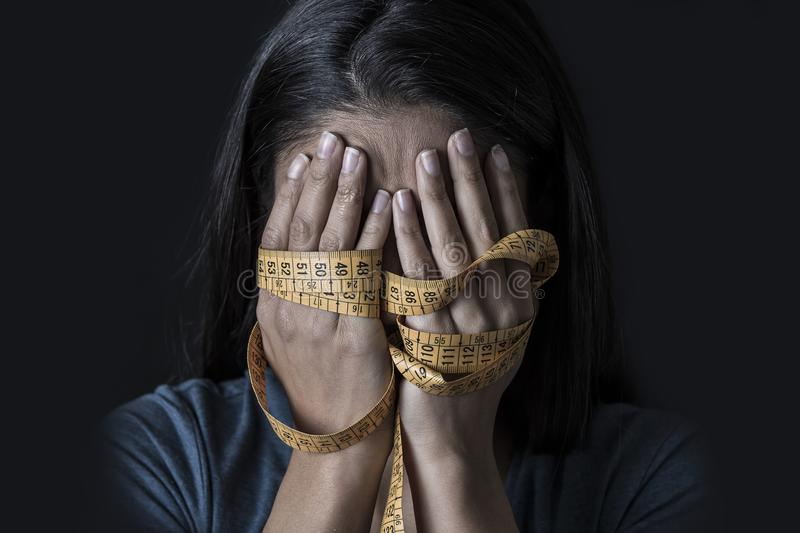 Hands wrapped in tailor measure tape covering face of young depressed and worried girl suffering anorexia or bulimia nutrition dis. Close up hands wrapped in royalty free stock photography