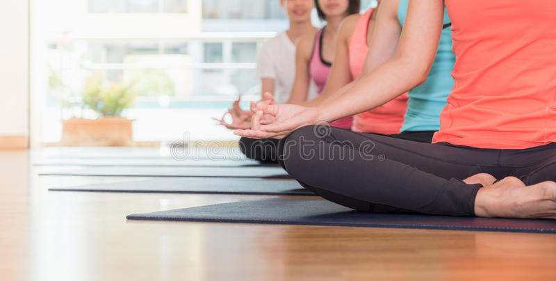 Close up hands of yoga group seated doing Hand Mudra and meditates in a training studio fitness room, Calm and relax. Concept,wellness and healthy lifestyle royalty free stock photo