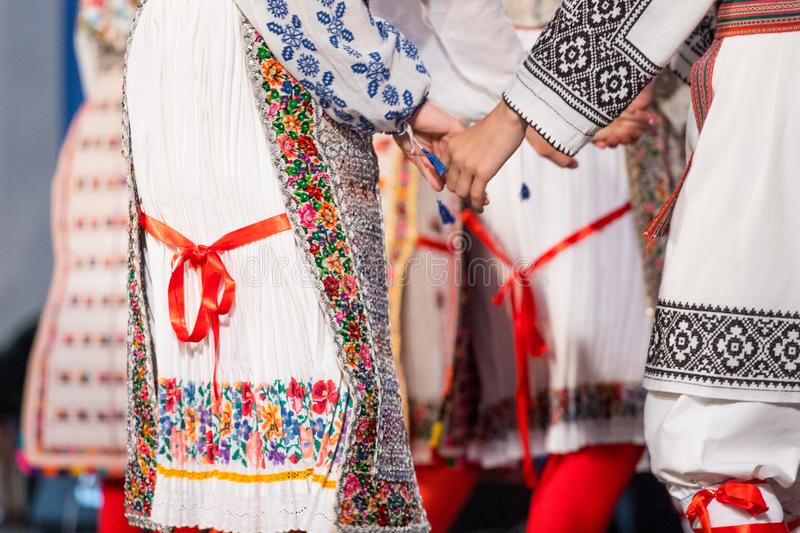Close up on hands of young Romanian dancers perform a folk dance in traditional folkloric costume. Folklore of Romania.  stock image