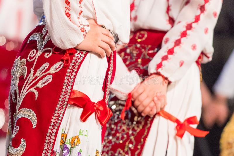 Close up on hands of young Romanian dancers perform a folk dance in traditional folkloric costume. Folklore of Romania stock photos