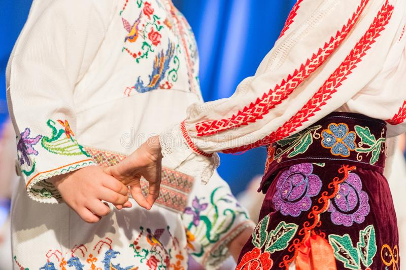 Close up of hands of young Romanian dancers perform a folk dance in traditional folkloric costume. Folklore of Romania.  royalty free stock image