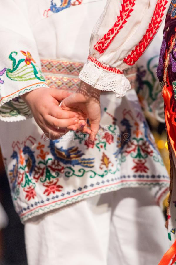 Close up of hands of young Romanian dancers perform a folk dance in traditional folkloric costume. Folklore of Romania.  royalty free stock photos