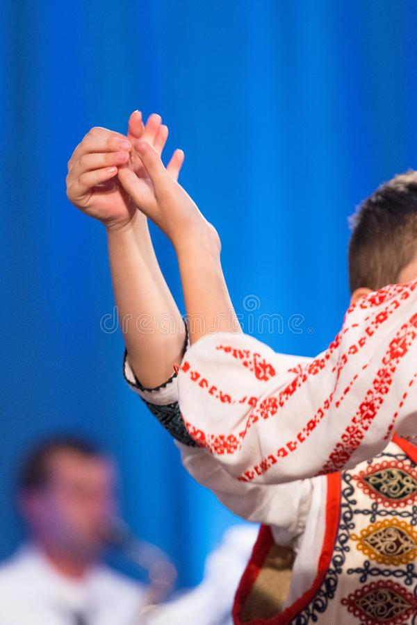Close up of hands of young Romanian dancers perform a folk dance in traditional folkloric costume. Folklore of Romania stock photos