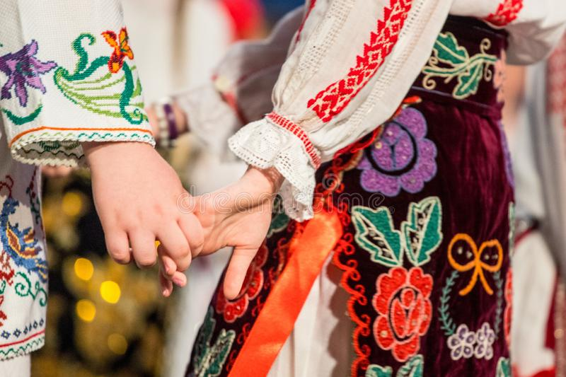 Close up of hands of young Romanian dancers perform a folk dance in traditional folkloric costume. Folklore of Romania.  stock image