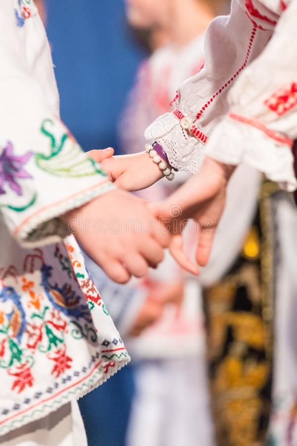 Close up of hands of young Romanian dancers perform a folk dance in traditional folkloric costume. Folklore of Romania.  stock photography
