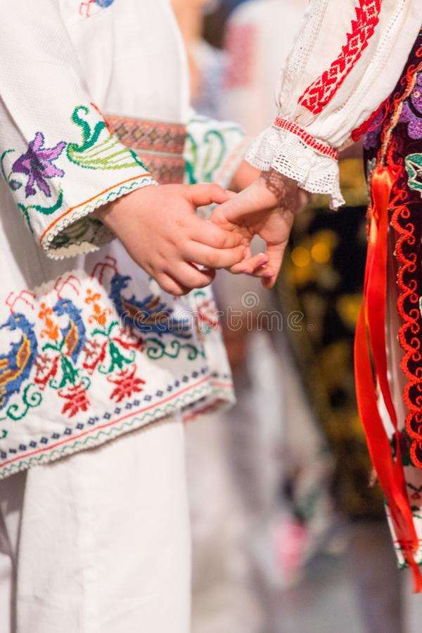 Close up of hands of young Romanian dancers perform a folk dance in traditional folkloric costume. Folklore of Romania.  royalty free stock photo