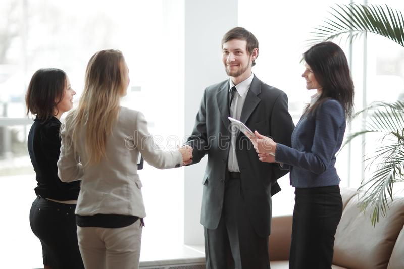 Close up.handshake business partners and applauding business team. royalty free stock photography