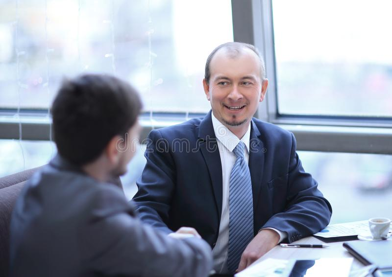 Close up.handshake of business partners sitting at a Desk. Concept of partnership stock images