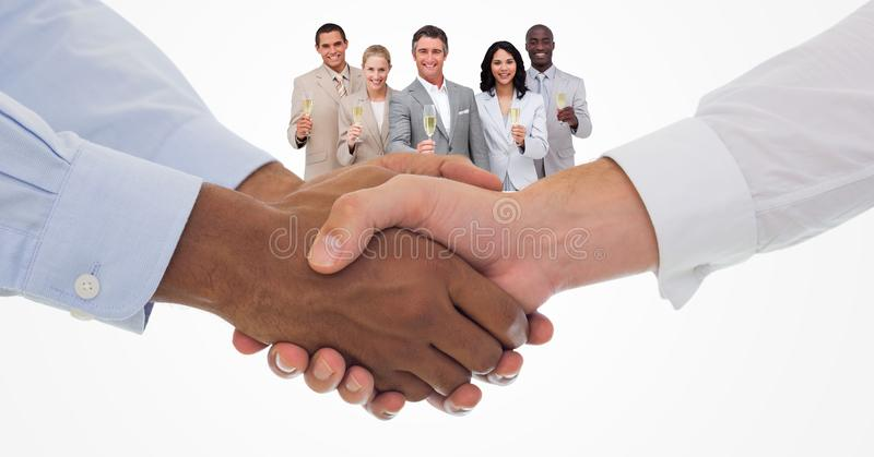 Close-up of handshake with colleagues holding champagne flutes in background stock images