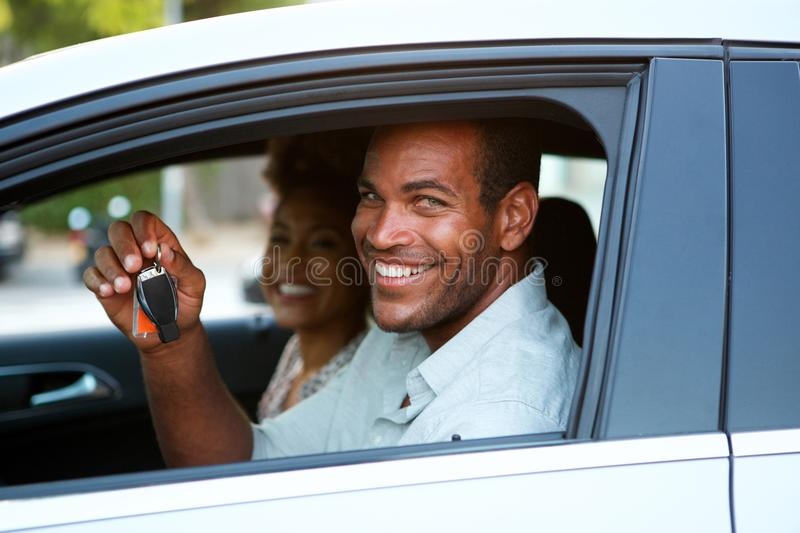 Close up handsome African American couple sitting in car smiling. Close up portrait of handsome African American couple sitting in car smiling stock images